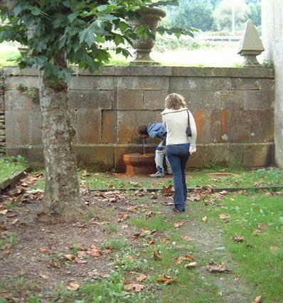 La fuente de agua de hierro, junto a la primera casa. Aparecen los hijos de él en una visita cursada en 2003.